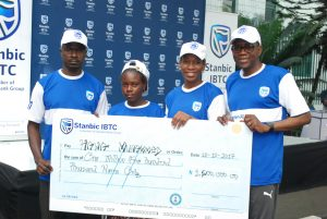 "Chief Executive, Stanbic IBTC Holdings Plc, Mr. Yinka Sanni; Non-Executive Director, Stanbic IBTC Holdings Plc, Mrs. Ngozi Edozien; a beneficiary prosthetic limbs & education trust  donated by Stanbic IBTC, Hawa Mohammed; Father of the beneficiary, Mr. Mohammed during the presentation of cheques to beneficiaries of Stanbic IBTC 2017 ""Together For A Limb"" CSI Initiative in Lagos, on Saturday, 28 Oct, 2017"