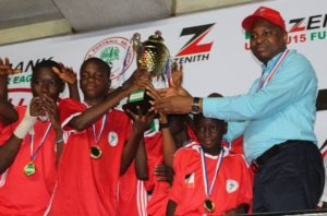 Group Zonal Head, Akwa Ibom, Zenith Bank Plc, Mr. Asuquo Ita, presenting the U-13 trophy to the South-West Team