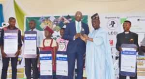 GIVING BACK TO OUR CUSTOMERS   The Executive Director, Corporate Bank, Fidelity Bank Plc, Obaro Odeghe (5th left) receives an award on behalf of the bank from the President, Lagos Chamber of Commerce & Industry (LCCI), Babatunde Ruwase during the bank's Special Day on Wednesday at the 2019 Lagos International Trade Fair while beneficiaries of Fidelity Loyalty Scheme – Uchenna Benedict Anyamaele; Oniyeyone Honeybell Ogunye; Ogochukwu Ijeoma Ugwu; Victoria Adebukola Oloyede, and Ofuremen Marvellous – look on.