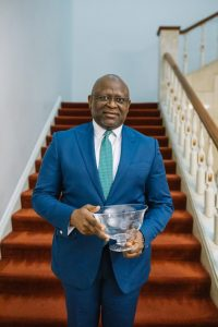 An excited Dr. Adeduntan proudly displaying his award, shortly after receiving it.